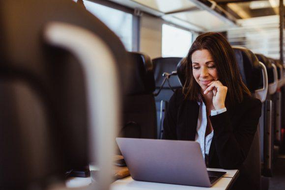 kvinna som arbetar vid dator på tåg